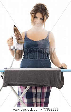Cheerful housewife with a beautiful smile standing at the ironing board ironing clothes