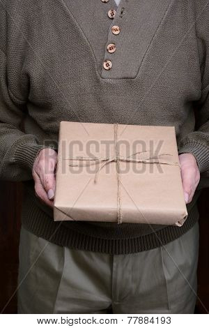 Closeup of a man holding a parcel in front of his torso.