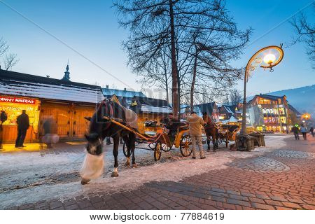 ZAKOPANE, POLAND - DECEMBER 4, 2014: Famous Krupowki street in Zakopane at winter time. Krupowki street is the main shopping area and pedestrian promenade in the center of Zakopane, Poland.