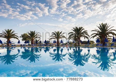 Palm Trees, Beach Sunbeds And Umbrellas Near The Pool By The Sea