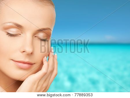beauty, people, vacation and health concept - beautiful young woman touching her face over blue sea and sky background