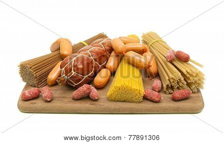 Different Types Of Pasta And Sausages On A Cutting Board. White Background.