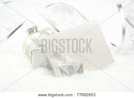 Silver Christmas Decoration On Snow With Wishes Card