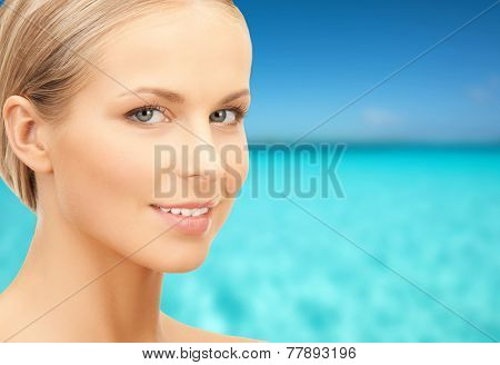 beauty, people and health concept - beautiful young woman face over blue sky and sea background