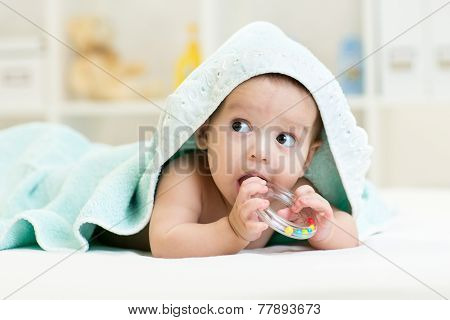 Cute baby with teether under towel indoor