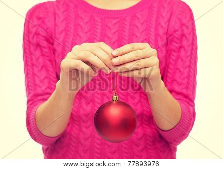 christmas, decoration, holidays and people concept - close up of woman in pink sweater holding christmas ball