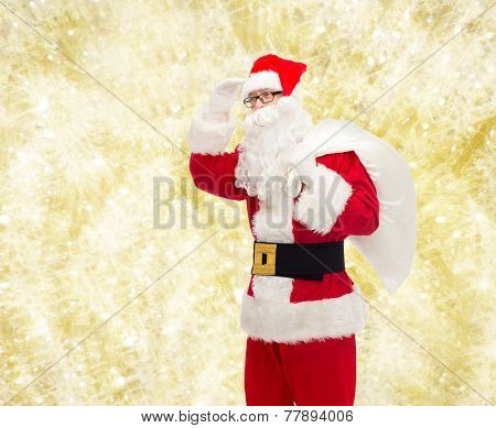 christmas, holidays and people concept - man in costume of santa claus with bag looking far away over yellow lights background