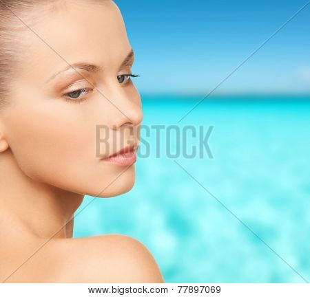 people and beauty concept - beautiful young woman over blue sky and sea background
