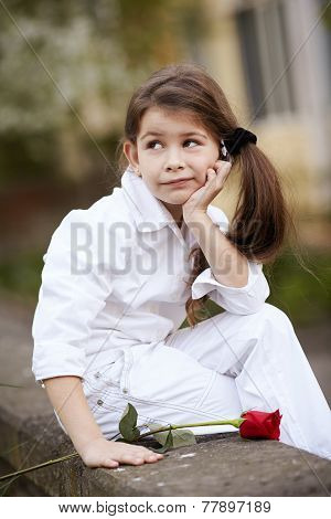 pretty girl smell rose outdoor in white suit