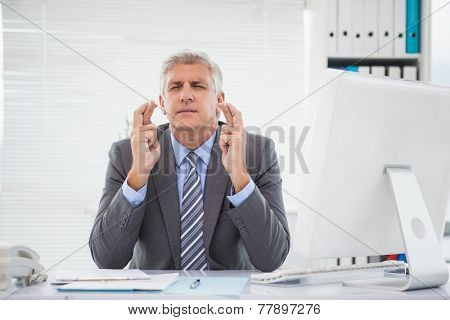 Wishing businessman crossing his fingers in his office