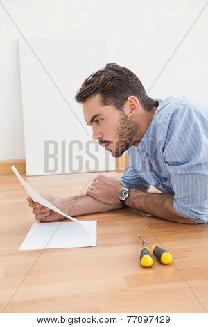 Casual man reading instruction manual for power tool at home in the living room