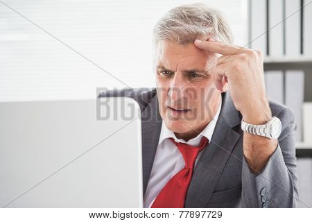 Confused businessman looking at his laptop in his office