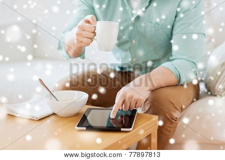 technology, home, drinks, food and lifestyle concept - close up of man with tablet pc computer and cup having breakfast at home