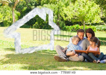 Family looking at their photo album in the park against house outline in clouds