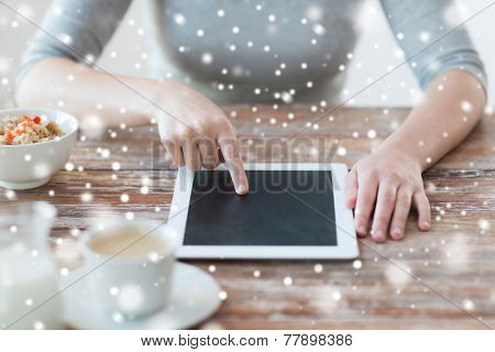 health, technology, internet, food and home concept - close up of woman pointing finger to tablet pc computer screen and having breakfast