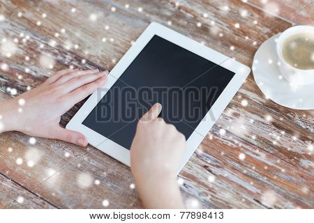 technology, people and home concept - close up of female hands pointing finger to black blank tablet pc computer screen