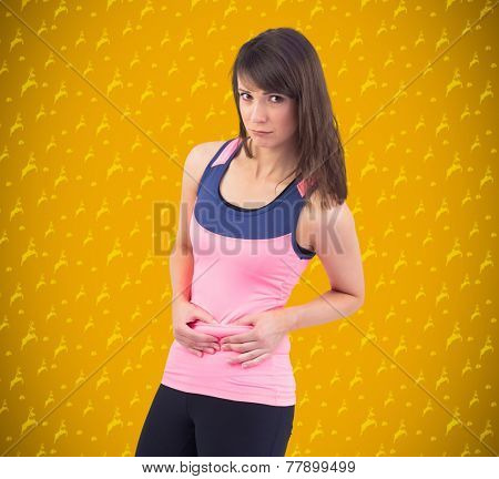 Festive fit brunette pinching her stomach against yellow background with vignette
