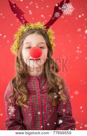 Festive little girl wearing red nose against snow falling