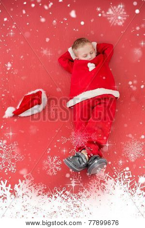 Little boy napping in santa costume against snow falling
