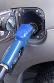 stock photo of vacuum pump  - Blue fuel nozzle in pouring to car - JPG