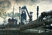 pic of polution  - Smokestacks in factory with yellow smoke and clouds - JPG