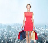 shopping, sale and holidays concept - smiling elegant woman in red dress with shopping bags over cit poster