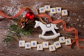 stock photo of wooden horse  - christmas card with greetings made of letter cubes with vintage wooden rocking horse on wooden background - JPG