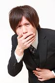 stock photo of vomiting  - portrait of young Japanese businessman vomit on white background - JPG