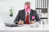 picture of overwhelming  - Overwhelmed businessman with sticky notes on head in his office - JPG