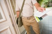 stock photo of postman  - Postman delivering a letter outside a home - JPG