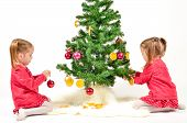 stock photo of twin baby girls  - Twin Girls are decorating Christmass Tree with home made Ornaments isolated on white Background - JPG