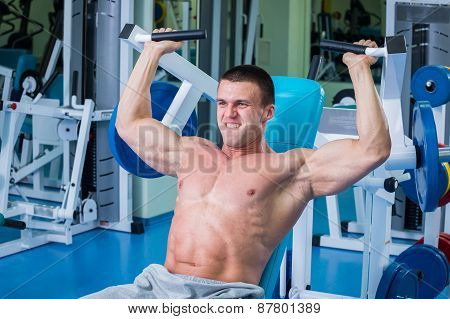Fit man exercising at the gym on a machine.Man at the gym.