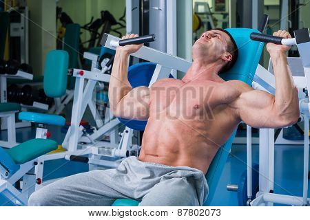 Fit man exercising at the gym on a machine.Man at the gym