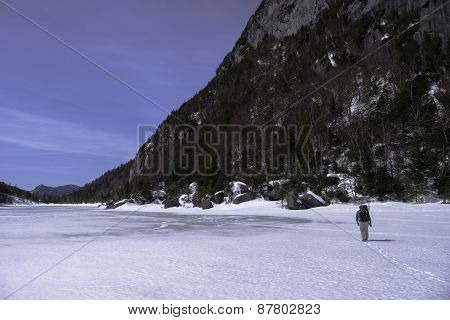 Man Trecking Across A Frozen Lake