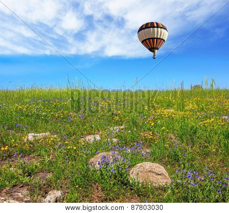 In a clear sky flying big colorful balloon. Flowering Golan Heights in a beautiful sunny day