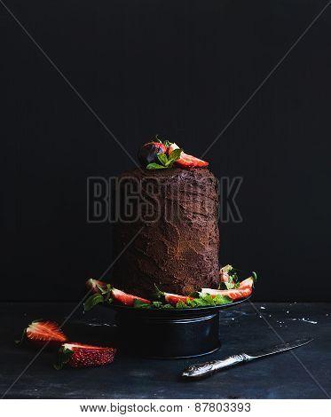 Chocolate high cake with strawberry, dark background