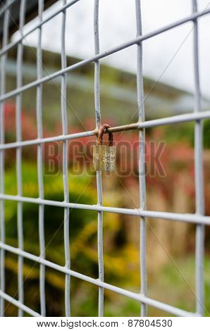 Locked Padlock On Square Metal Fence - Vertical
