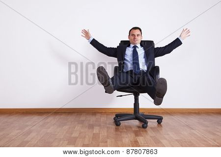 Businessman having fun with his chair