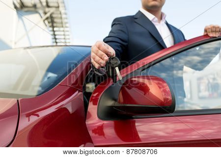 Closeup Shot Of Handsome Car Salesman Giving Keys