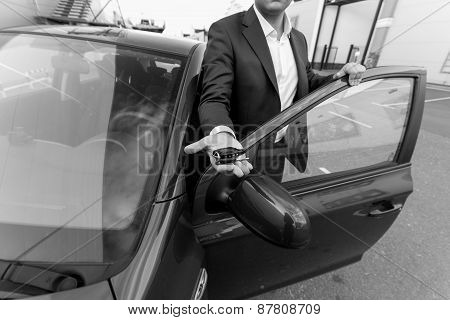 Black And White Closeup Of Car Sales Manager Holding Key On Hand