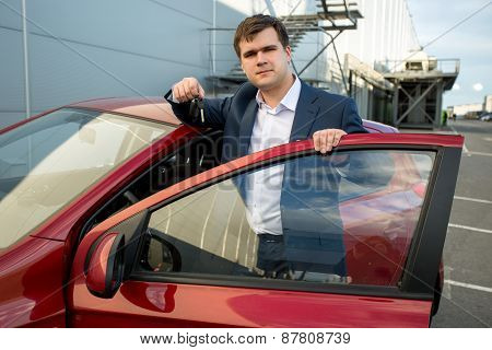Handsome Man In Suit Leaning Against New Car And Showing Keys