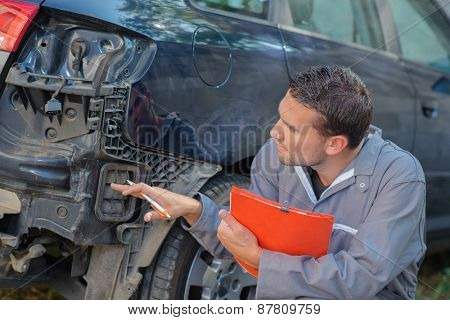 Mechanic inspecting damaged car