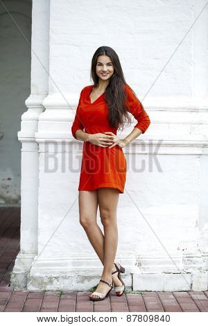 Beautiful young woman in red dress against the background of a block of stone wall