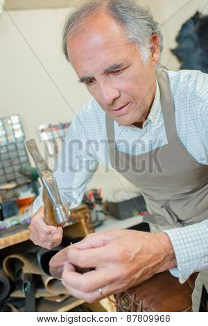 Cobbler hammering a pair of shoes