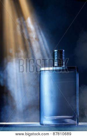 dramatic photo of perfume bottle with smoke and light rays