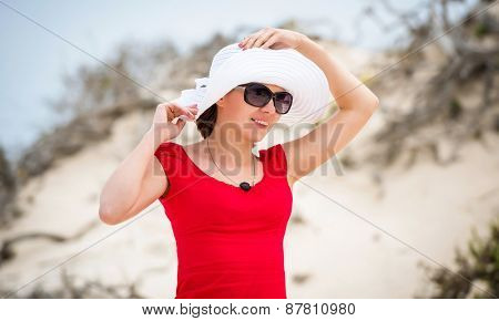 beautiful young woman in evening red dress and white hat on a background of a sand desert