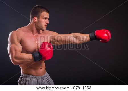 The man in red boxing gloves on a dark background.