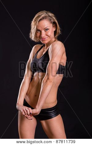 Sexy athletic blonde posing on a black background. Muscular girl on a black background.