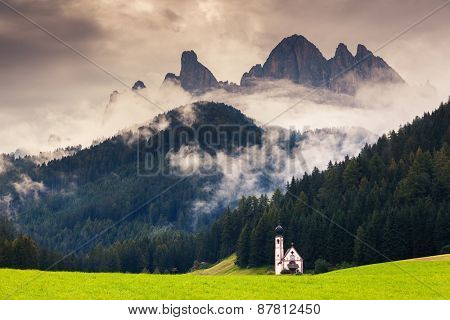 Countryside foggy view of the Santa Maddalena in the National Park Puez Odle or Geisler summits (Val di Funes) Dolomites, South Tyrol. Location Bolzano, Italy, Europe. Dramatic scene. Beauty world.