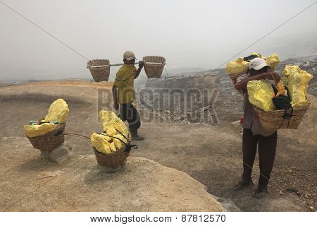 KAWAH IJEN, INDONESIA - AUGUST 8, 2011: Miners carry baskets with sulphur in toxic volcanic gas from the sulphur mines in the crater of the active volcano of Kawah Ijen, East Java, Indonesia.